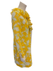 Side view of a mannequin in a long sleece 1960s mini dress with ruffles at the neck, front, and sleeves. The dress is yellow with white and green flowers on it