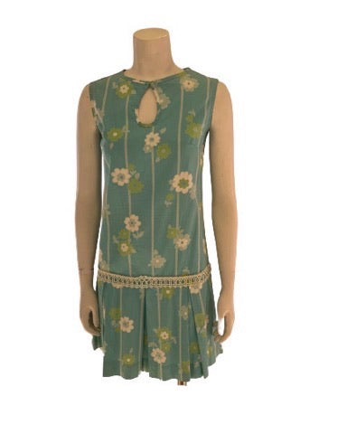 Front view of a mannequin wearing a light blue sleeveless mini dress with a white and green floral pattern