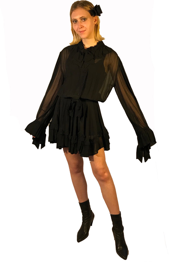 Sheer, long-sleeve, silk dress with bow at neck, and ruffles at wrist. Gathered waist. Length is above the knee.