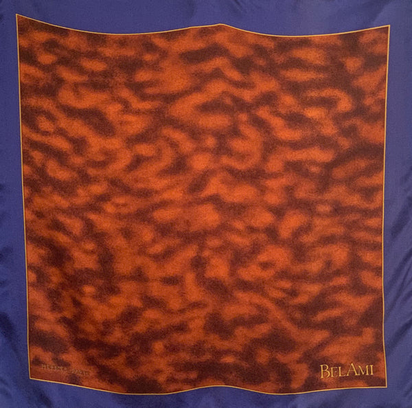 Small square silk pocket scarf  with a blue border, mottled brown center pattern and the word BELAMI on the right bottom corner.