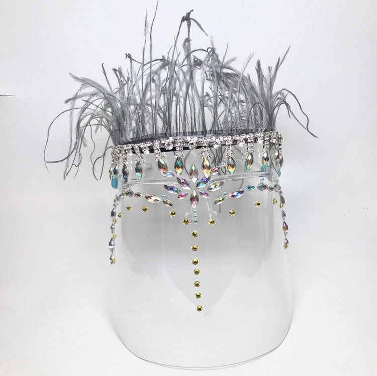 Clear face shield with rhinestones and crystals  with a grey feather trim on top Shield is worn on face with 2 arms that rest on the ears.
