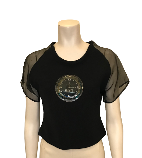 "Black polyester/rayon cropped top with sheer nylon sleeves and a plastic patch of a clock face with the words ""Time to Create"""