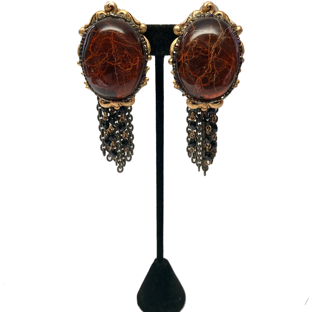 Ornate, faux-amber, clip-on earrings with encased plant roots. Metal-chain and black-beaded fringe.