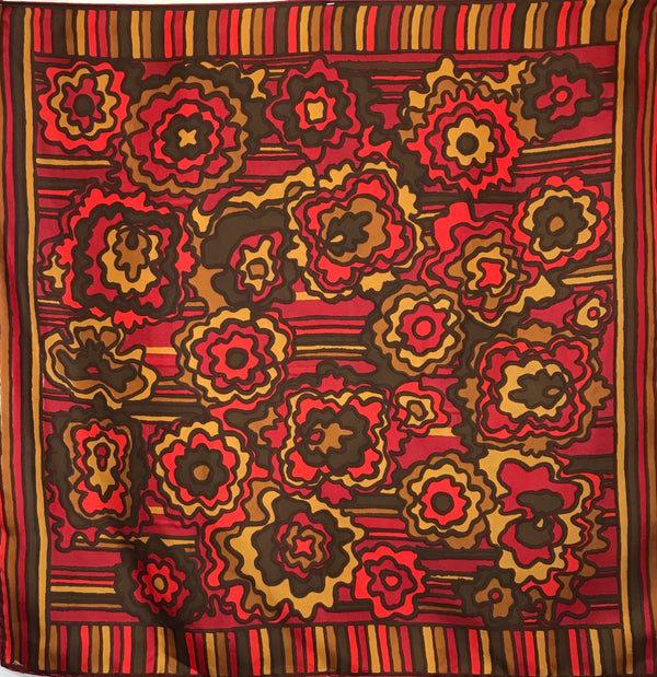 A silk scarf in shades of mustard yellow, brown, coral, and burgundy. The border features vertical stripes, and the center has horizontal stripes and flowers.