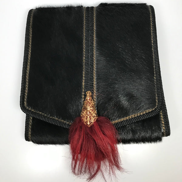 Black leatherr and pony hair fold over handbag with gold clasp and red fur accent and rope shoulder strap