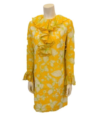 Front view of a mannequin in a long sleece 1960s mini dress with ruffles at the neck, front, and sleeves. The dress is yellow with white and green flowers on it