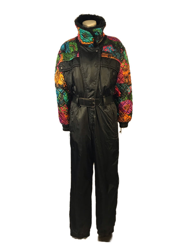 Black ski jumpsuit with a bright, patterned yoke & sleeves. Has attached belt and pockets on front.