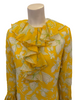Closeup front view of a mannequin in a long sleece 1960s mini dress with ruffles at the neck, front, and sleeves. The dress is yellow with white and green flowers on it