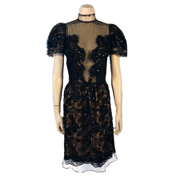 Short sleeve evening dress covered in lace and black beading. The front has a sheer insert. Skirt is knee length.