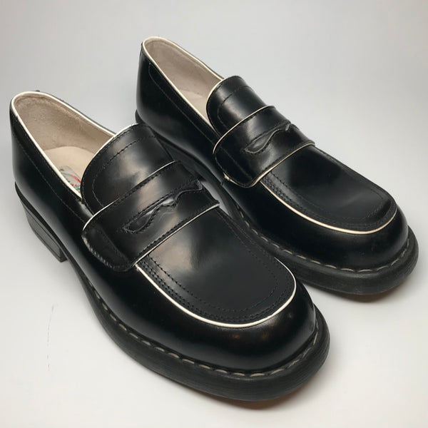 1990s black penny loafers with white trim and chunky soles