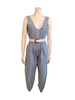 light blue chambray sleeveless jumpsuit with white trim and colored stone embellishment. Comes with white faux leather belt.