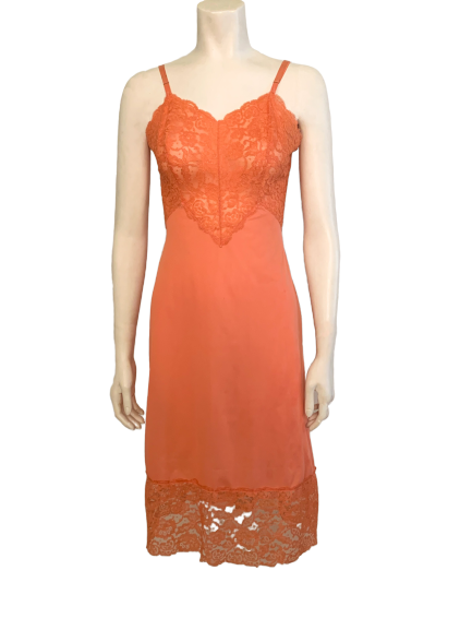 Front view of a mannequin in a coral 1950s slip with a lace top and bottom trim