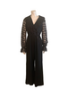 Front view of mannequin in a 70s black jumpsuit with long lace sleeves and a ruffle at the V neck