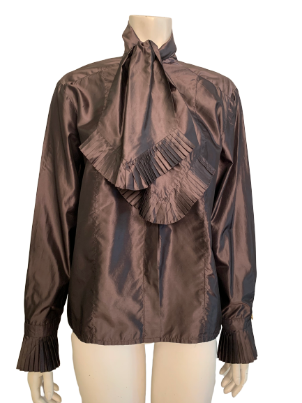 Iridescent copper silk blouse with long sleeves and a large bow at neck. Bottom of bow and cuff are trimmed  accordion pleats. Button down front