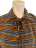 Closeup of blouse with horizontal stripes and dots in orange, brown, blue, red, and creme. The neckline has a straight collar and a tie at the neck