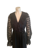 Closeup Front view of mannequin in a 70s black jumpsuit with long lace sleeves and a ruffle at the V neck