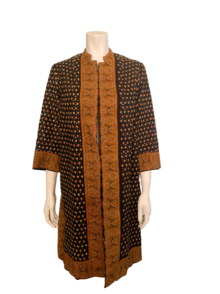 Full length front view of mannequin wearing tunic with black beaded paisley and orange paisley trim