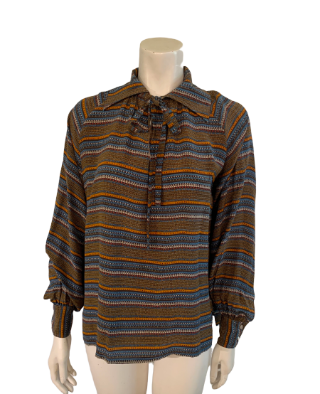 Front view of a mannequin in a long sleeve blouse with horizontal stripes in brown, orange, blue, and creme. Bow at the neck.