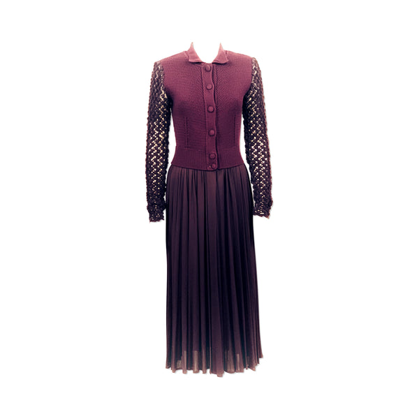 Full length front view of mannequin wearing a deep purple Jean Paul Gaultier dress with knit wool at the top, open crochet long sleeves, and draped rayon skirt.