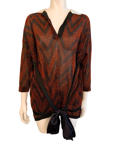 Front view of mannequin wearing long-sleeved, metallic red and black chevron print blouse with satin collar and waist tie