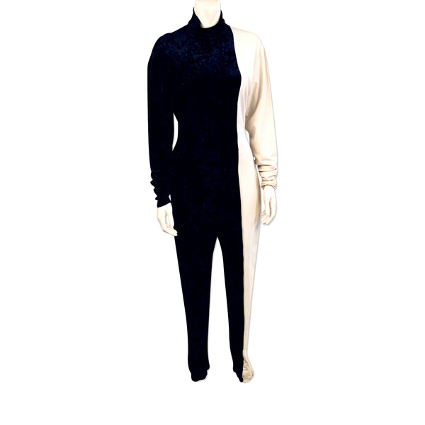 Full length view of mannequin wearing a half black velvet, half white jersey jumpsuit by Norma Kamali.