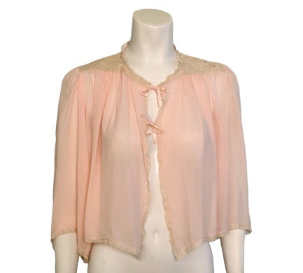 Front view of a light pink bed jacket on a mannequin