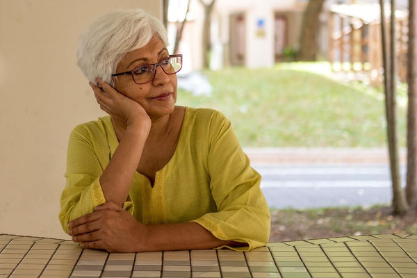Menopause and anxiety: An older woman rests her head on her hand and stares into the distance