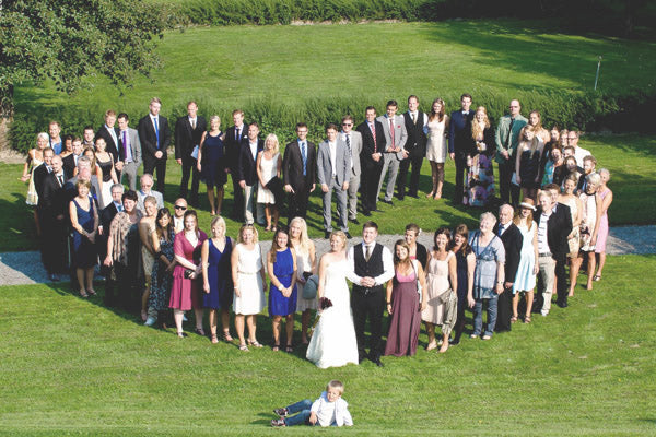 Wedding guests stand in a heart shape for an alternative wedding photo pose