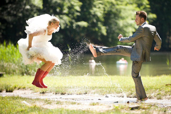 A childish bride wearing wellys and groom jump in puddles after a unique wedding