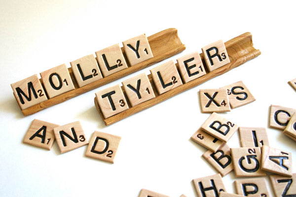 Scrabble tiles spell out a bride and grooms names as a creative photograph for their wedding photo album