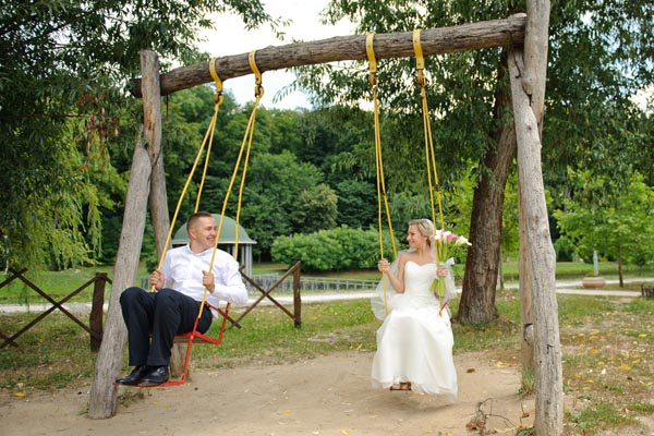 A bride and groom having fun playing on children's swings for an unusual wedding photo