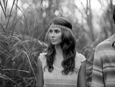 A beautiful, boho, hipster bride with a headband and long brown hair walks through a forest