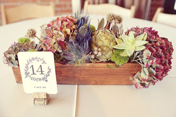 A trough of flowers and a table number placed in the centre of a dining table at a natural wedding