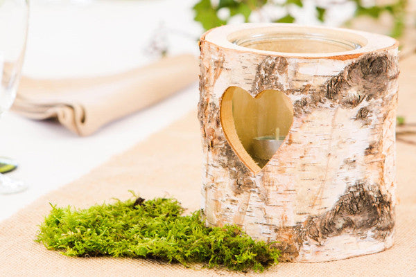 A rustic wood slice candle holder surrounded by moss decorates a nature themed wedding reception