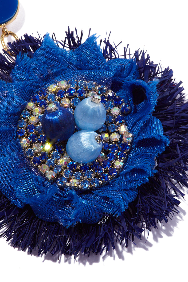 AURORAH Dangle Flower Earrings - Deep Blue Jewelry   Deep Blue  Aurorah Dangle Flower Earrings - Deep Blue Close Up View Natural fiber and textile earrings Crystal and bead embellishments Stud round is .7″ Flower dangle is 3″ Earrings dust or dangle an inch or so above most shoulders Made in the USA