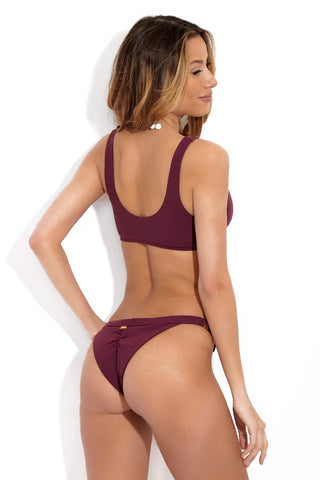 BEACH BUNNY Rib Tide Bottom - Purple Plum Bikini Bottom | Purple Plum| Back View of Beach Bunny Rib Tide Bikini Bottom in Purple Plum Color with Cheeky Coverage, Ruched Butt, and Adjustable Side Straps
