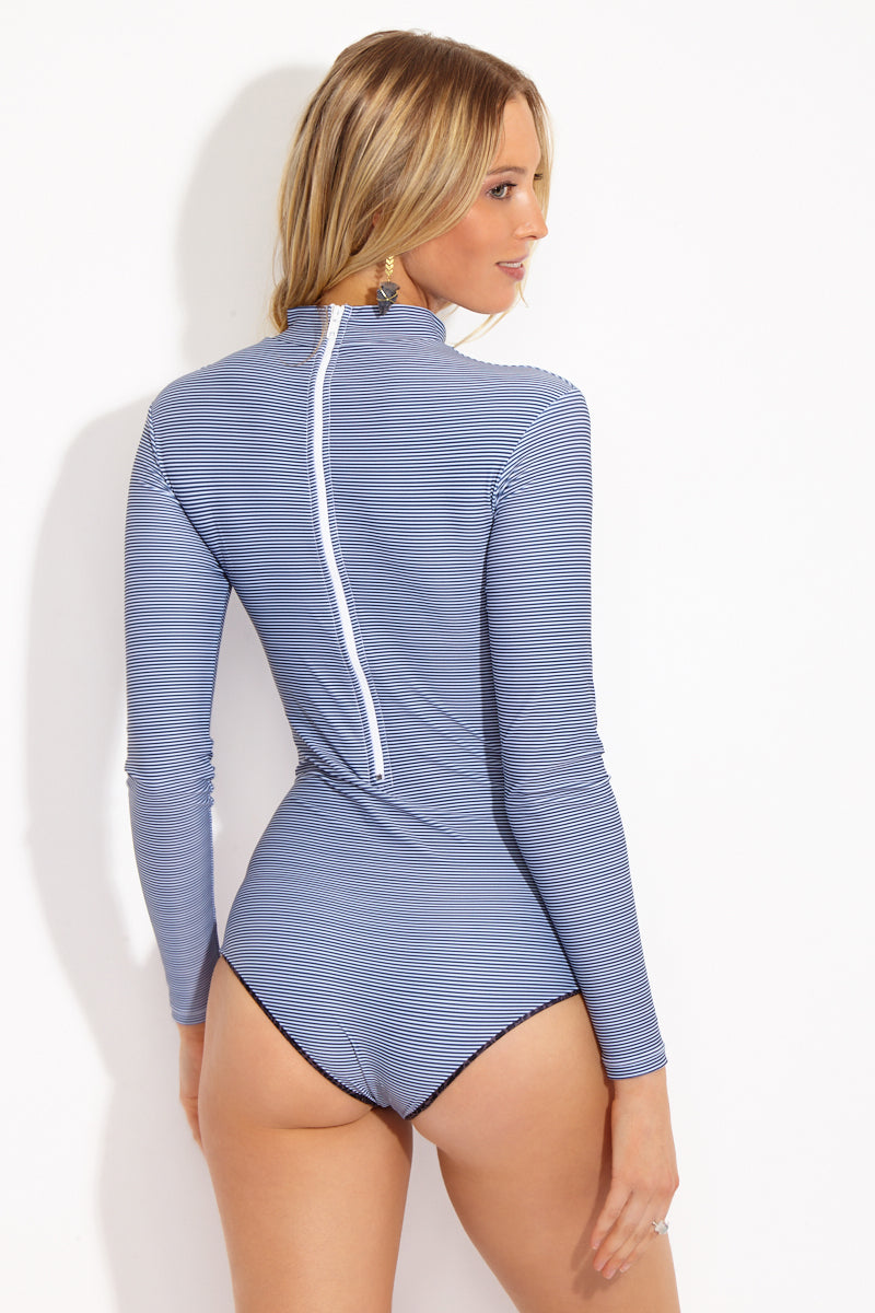 ACACIA Ehukai Longsleeve One Piece - Long Island One Piece | Long Island| Acacia Ehukai Longsleeve One Piece - Long Island Back View Long sleeve one piece swimsuit with high neck. Thin dark blue and white horizontal stripe print. Mid-rise leg cut. White zipper back closure. Moderate coverage.