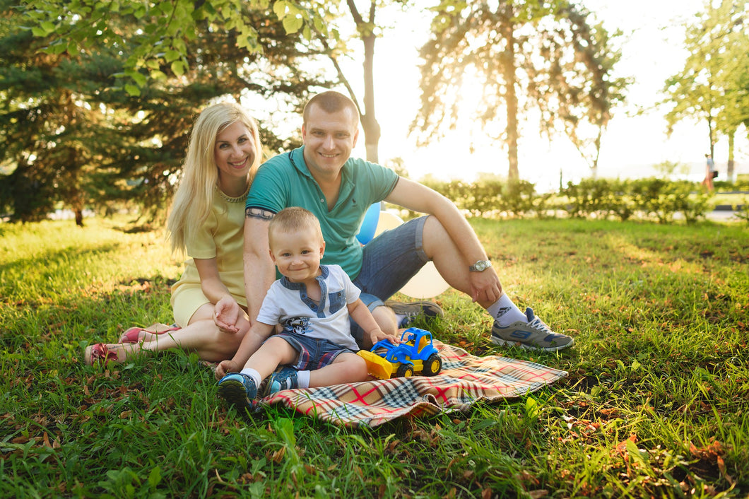 photo of family sitting in the grass smiling out in nature