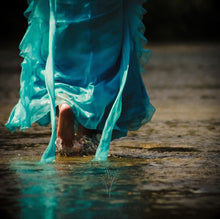 Load image into Gallery viewer, Photo of a person in a blue dress walking through low water