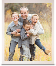 "Load image into Gallery viewer,  11"" x 14"" White Framed Print photo of a three young boys laughing with their father holding them, all of them are smiling (portrait)"