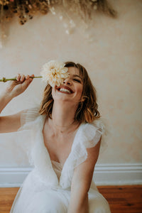 bride-holding-flower-and-smiling