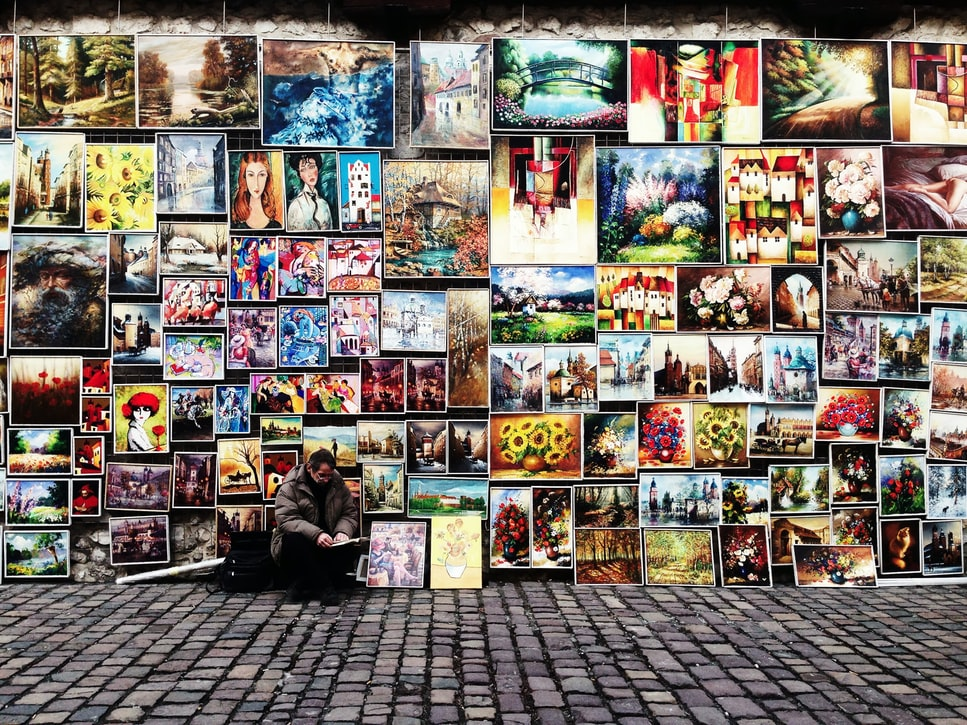 man sitting by wall of paintings