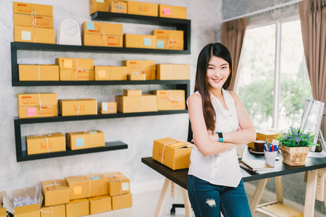 female store owner standing by boxes in her home