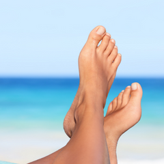 lovely looking feet with bright blue sea in the background