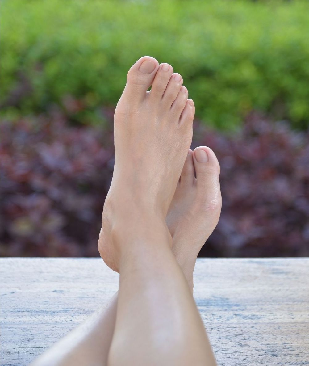 smooth, soft looking feet resting on a wooden balcony