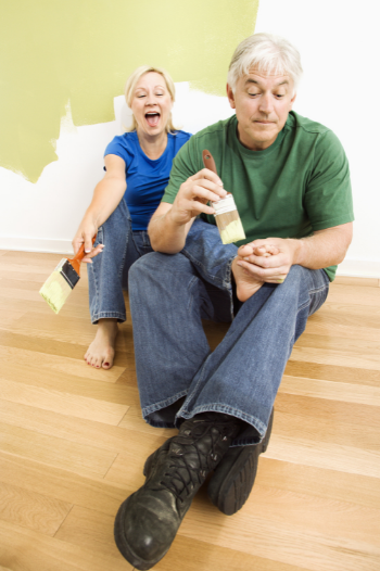 man painting woman's toenails with a house painting brush