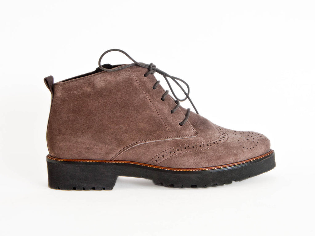 Side view of grey brown suede brogue style ladies ankle boots with flat black heel and sole and skinny laces