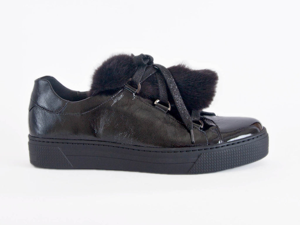Side view of black patent leather trainer shoe with distinctive big fur tongue on top, slightly sparkly laces and thick flat black sole