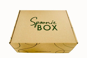 An image of a Spoonie Box: a rectangular, recycled cardboard box with the Spoonie Box logo on top and a wavy line design on the sides