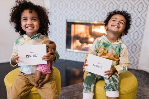 two smiling black and brown kids with affirmation cards